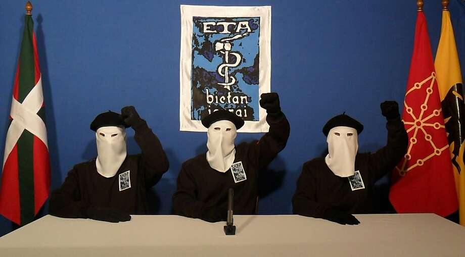 "UNSPECIFIED - UNDATED:  In this undated image provided by Gara, three Eta militants pose in front of the group's symbol of a snake coiled around an axe, in support of a declaration released on October 20, 2011 stating a ""definitive cessation"" to it's four decade long campaign of armed conflict in seeking an independent Basque homeland from Spain and France.  (Photo released by Gara via Getty Images) Photo: Handout, Gara Via Getty Images"