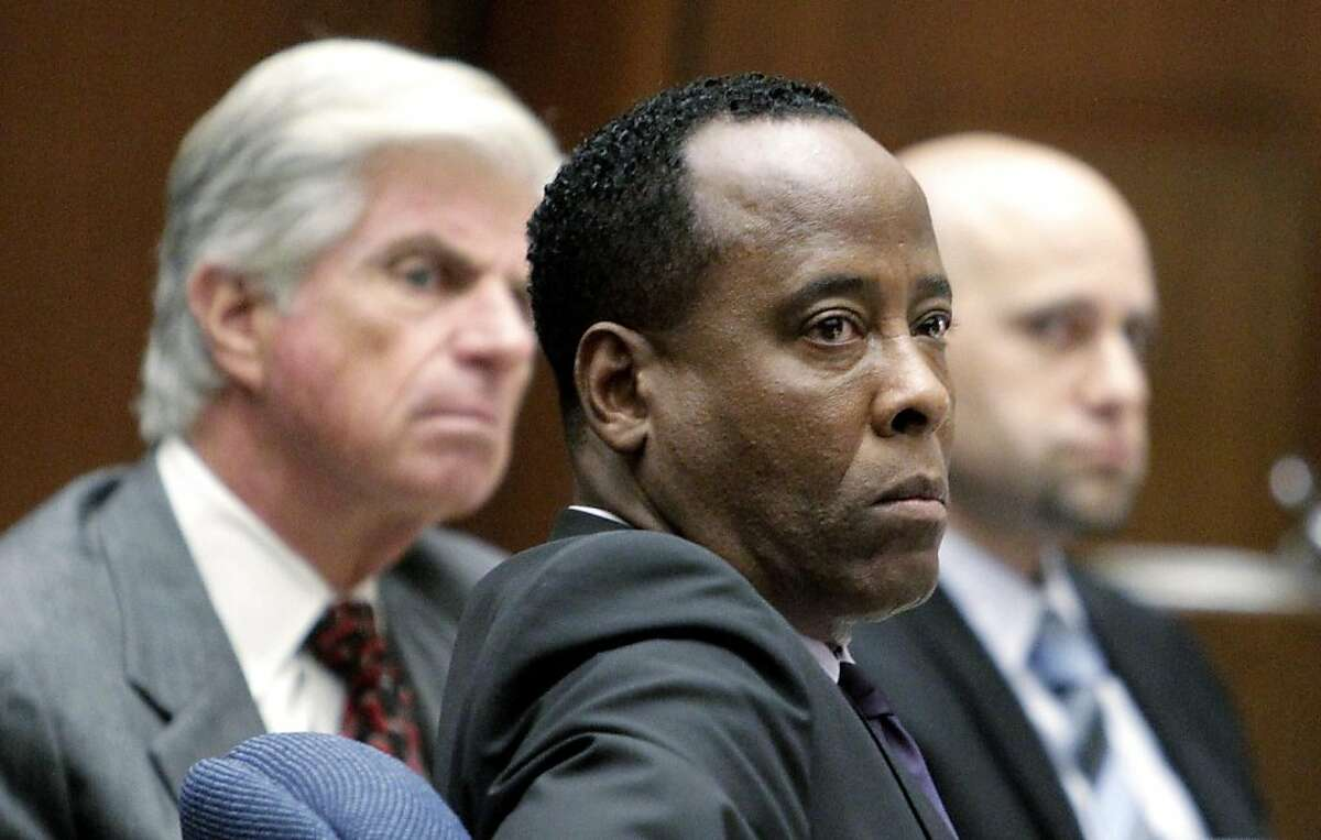 LOS ANGELES, CA - OCTOBER 19: Dr. Conrad Murray (C) looks on beside his lawyers J. Michael Flanagan (L) and Nareg Gourjian during Murray's involuntary manslaughter trial on October 19, 2011 in downtown Los Angeles, California. Murray, who is accused of killing Michael Jackson, faces a possible four year in prison sentence and the loss of his medical license if convicted on the charge of involuntary manslaughter. (Photo by Reed Saxon-Pool/Getty Images)
