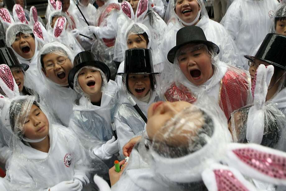 Children from Gordon J Lau school open their mounths hoping to get a candy treat while waiting for the annual San Francisco Chinese New Year's parade to start Saturday Feb 19 2011. This years event ushered in the Year of the Rabbit! As thousands of on lookers filled San Francisco streets. Photo: Lance Iversen, The Chronicle