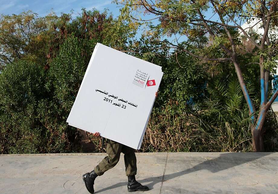 A soldier carries ballot boxes to a polling station in Mnihla, near Tunis, Saturday, Oct. 22, 2011. Tunis was filled with rival rallies throbbing with music as the political parties marked the end of three weeks of campaigning for the country's first truly free and multiparty elections since its independence from France in 1956. (AP Photo/Amine Landoulsi) Ran on: 10-23-2011 A soldier carries ballot boxes to a polling station for the first truly free elections in Tunisia. Photo: Amine Landoulsi, AP