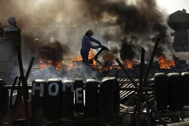 An Irish traveller resident picks up the burnt remains of a piece of furniture by a burning barricade during evictions at the Dale Farm travelers site near Basildon, 30 miles (50 kilometers) east of London, Wednesday, Oct. 19, 2011. British police in riot gear used sledgehammers and crowbars Wednesday to clear the way for the eviction of Irish Travelers from a site where they have lived illegally for a decade. (AP Photo/Matt Dunham) Ran on: 10-23-2011 Below, far left: An Irish Traveler resident picks up the charred remains of a piece of furniture by a burning barricade. Photo: Matt Dunham, AP