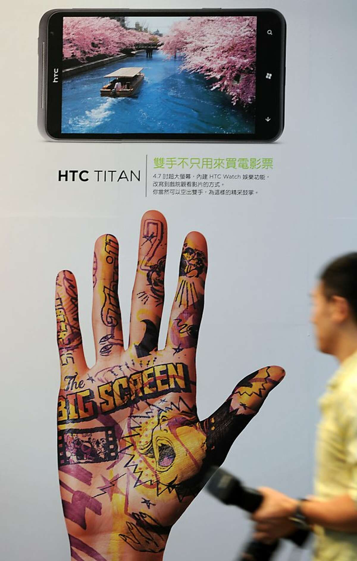 A man walks past a poster showing the latest HTC smartphone