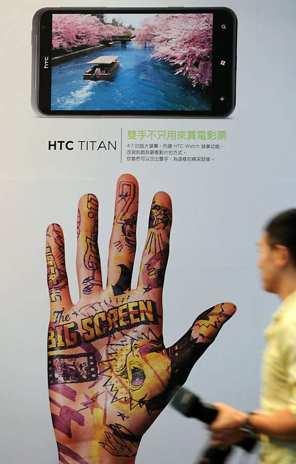 """A man walks past a poster showing the latest HTC smartphone """"Titan"""" as the company previews its latest product at a press conference in Taipei on October 12, 2011. Taiwan's leading smartphone maker HTC unveiled its first cellphones running on Microsoft's much-anticipated software platform """"Mango"""" after Apple launched its latest iPhone version.  AFP PHOTO / Sam YEH (Photo credit should read SAM YEH/AFP/Getty Images)  Ran on: 10-18-2011 HTC is seeking to block U.S. sales of the iPhone, iPod Touch and iPad. Photo: Sam Yeh, AFP/Getty Images"""
