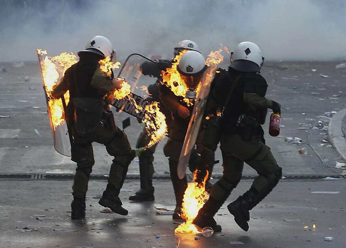Riot policemen assist colleagues whose clothing caught fire after being hit by a petrol bomb during rioting in central Athens, Thursday, Oct. 20, 2011. A protester died and dozens were injured during an anti-austerity demonstration that turned violent in the Greek capital, hours before lawmakers were to vote on deeply unpopular new cutbacks demanded by creditors to keep Greece financial solvent.(AP Photo/Petros Giannakouris)