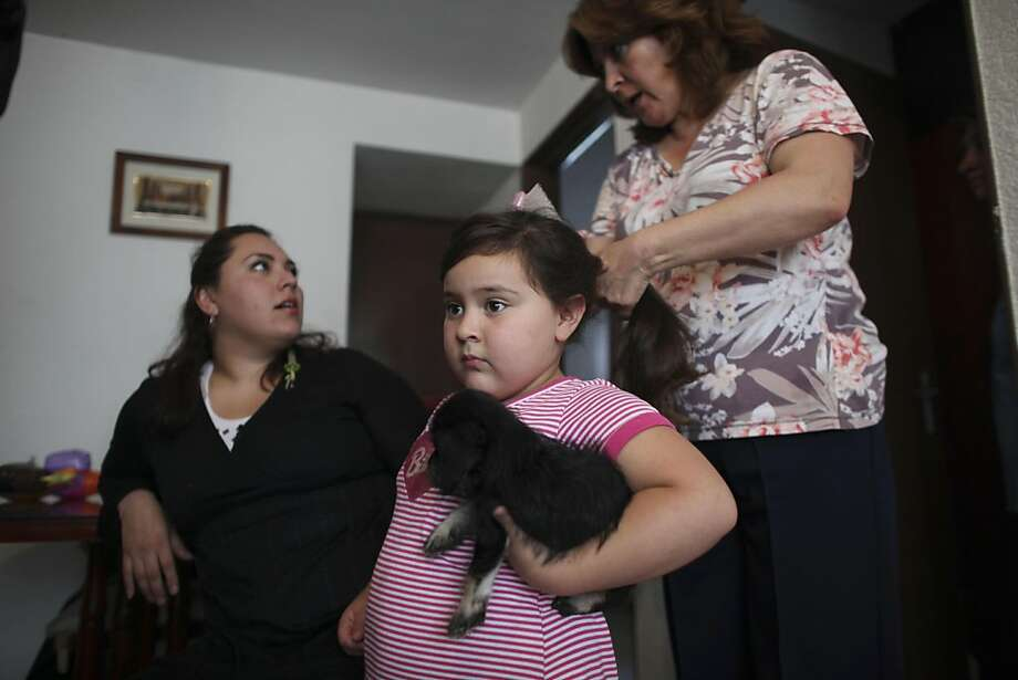 In this photo taken on Tuesday July 19, 2011, Elizabeth Sucilla combs the hair of her four-year-old granddaughter Anghella Torres before going out for a walk, at their home in Mexico City. Anghella weighs 66 pounds (30 kilos) - twice what she should. With the help of her grandmother, Anghella is following a modest diet and exercise program established for her by a nurse at a local public hospital earlier this year. Anghella's mother, Livni Schroeder, 25, is pictured at left. (AP Photo/Alexandre Meneghini) Photo: Alexandre Meneghini, AP