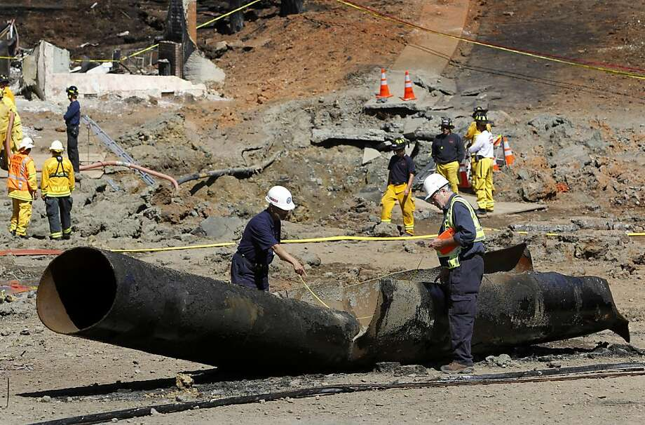 Federal investigators examine a 40-foot section of pipeline on Glenview Drive in San Bruno, Calif. on Saturday, Sept. 11, 2010. Four people were killed and more than 35 homes destroyed after the pipeline exploded creating a large crater (background).  Ran on: 09-12-2010 Photo caption Dummy text goes here. Dummy text goes here. Dummy text goes here. Dummy text goes here. Dummy text goes here. Dummy text goes here. Dummy text goes here. Dummy text goes here.###Photo: blast12_PHsection1284076800SFC###Live Caption:Federal investigators examine a 40-foot section of pipeline on Glenview Drive in San Bruno on Saturday. At least four people were killed and more than 35 homes destroyed after the pipeline exploded creating a large crater (background).###Caption History:Federal investigators examine a 40-foot section of pipeline on Glenview Drive in San Bruno, Calif. on Saturday, Sept. 11, 2010. Four people were killed and more than 35 homes destroyed after the pipeline exploded creating a large crater (background).###Notes:###Special Instructions:**MANDATORY CREDIT FOR PHOTOG AND SF CHRONICLE-NO SALES-MAGS OUT-TV OUT-INTERNET: AP MEMBER NEWSPAPERS ONLY** Photo: Paul Chinn, The Chronicle
