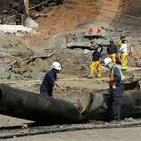 Federal investigators examine a 40-foot section of pipeline on Glenview Drive in San Bruno, Calif. on Saturday, Sept. 11, 2010. Four people were killed and more than 35 homes destroyed after the pipeline exploded creating a large crater (background).