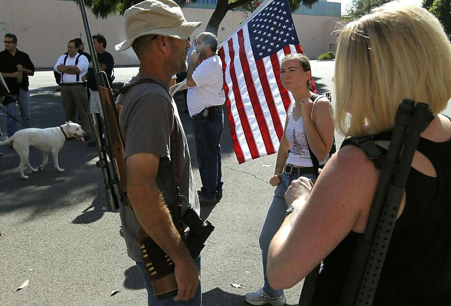 "(left to right) Chris Pelton, of Alameda, Tianna Klineburger, of Alameda and  Michelle Puphal, of San Jose display their firearms as they join fellow protesters in San Leandro, Ca., on Saturday October 22, 2011. Gun owners carry ""long guns"", rifles, shotguns and hand guns to protest against measure AB 144 signed by Governor Jerry Brown that beginning January 1, 2012, bans the open carrying of handguns. Photo: Michael Macor, The Chronicle"