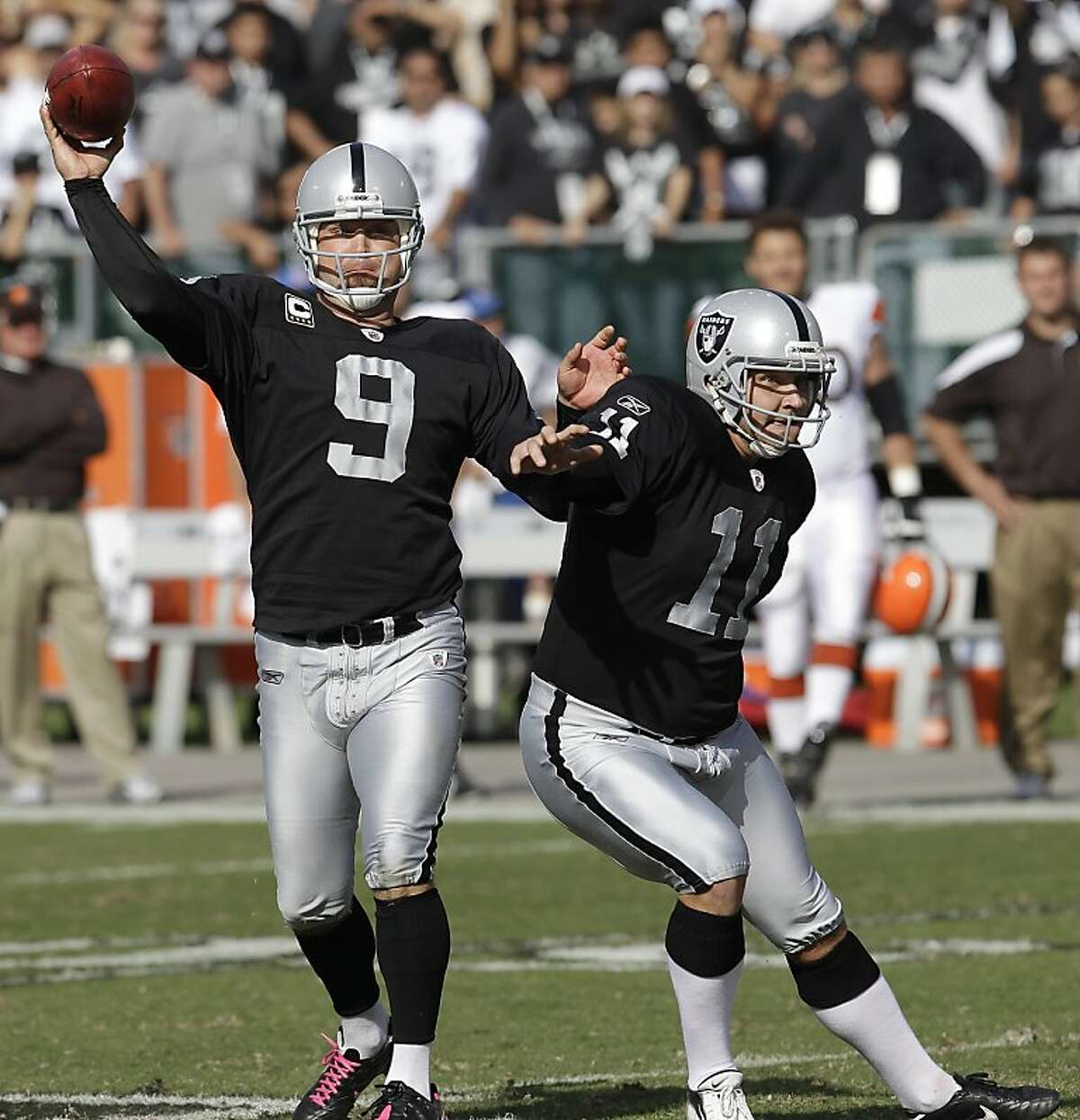 Oakland Raiders punter Shane Lechler (9) passes to tight end Kevin Boss (87) for a 35-yard touchdown pass on a fake field goal against the Cleveland Browns in the third quarter of an NFL football game in Oakland, Calif., Sunday, Oct. 16, 2011. Also pictured is Raiders place kicker Sebastian Janikowski (11).(AP Photo/Paul Sakuma)