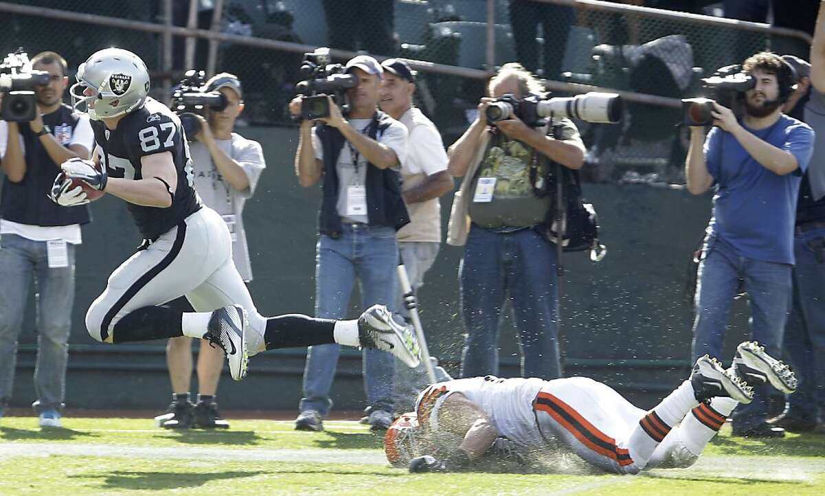 Oakland Raiders tight end Kevin Boss (87) scores past Cleveland Browns outside linebacker Chris Gocong (51) on a 35-yard touchdown pass from punter Shane Lechler (9) on a fake field goal in the third quarter of an NFL football game in Oakland, Calif., Sunday, Oct. 16, 2011. (AP Photo/Ben Margot)