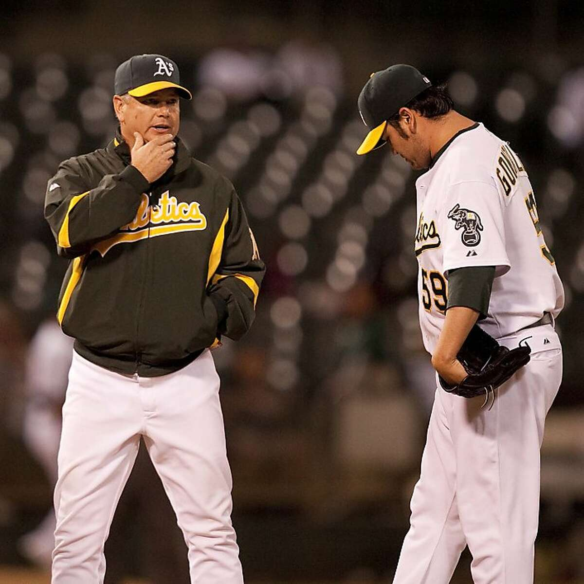 Pitching Coach Curt Young of the Oakland Athletics converses with pitcher Edgar Gonzalez (59) during the fourth inning against the visiting Texas Rangers at Oakland-Alameda County Coliseum in Oakland, Calif. on Monday, Sept. 21, 2009. Ran on: 09-22-2009 As pitcher Edgar Gonzalez (with pitching coach Curt Young) gave up six runs on nine hits over 31-3 innings. Ran on: 09-22-2009 As pitcher Edgar Gonzalez (with pitching coach Curt Young) gave up six runs on nine hits over 31-3 innings. Ran on: 08-24-2010 Curt Young