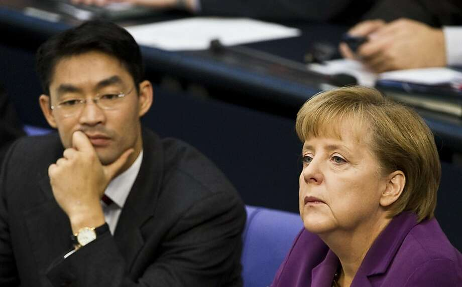 German Chancellor Angela Merkel (R) and German Economy Minister and vice-Chancellor Philipp Roesler take part in a session of the Bundestag lower house of parliament in Berlin October 21, 2011, during which parliamentarians debated on the European Stability pact, ahead of summit of EU leaders in Brussels that aims to thrash out a solution to the eurozone debt crisis. Roesler, who is also leader of the coalition government's junior partner, the Free Democrats (FDP), also ruled out raising Germany's 211-billion-euro (289-billion-dollar) contribution to the fund.     AFP PHOTO / JOHN MACDOUGALL (Photo credit should read JOHN MACDOUGALL/AFP/Getty Images) Photo: John Macdougall, AFP/Getty Images