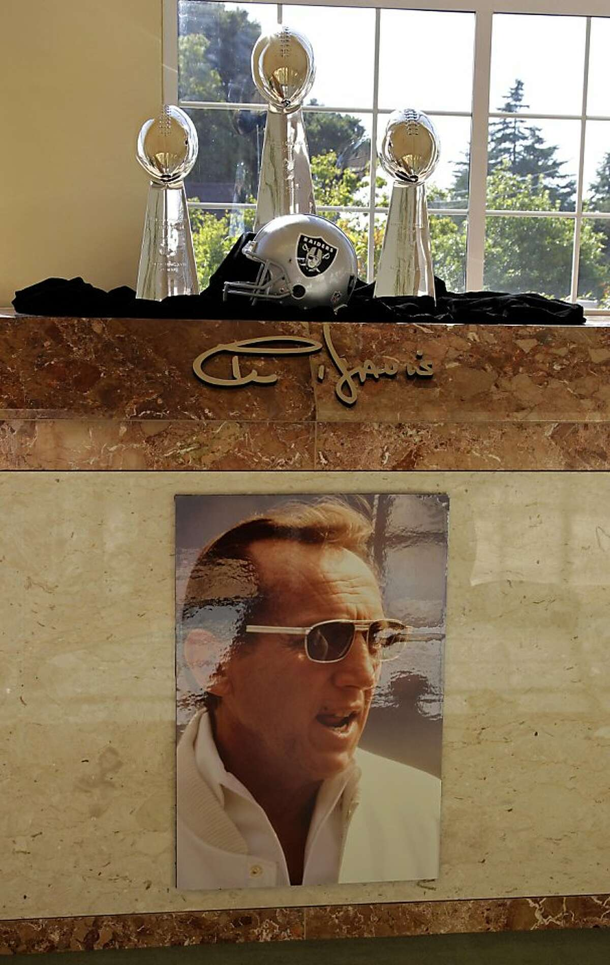 The crypt of Al Davis is seen adorned with an Oakland Raider helmet and three Super Bowl trophies Monday, Oct. 17, 2011, at the Chapel of the Chimes in Oakland, Calif. The final resting place of the Raiders former majority owner will be beside American blues singer-songwriter and guitarist, John Lee Hooker, and cost $100,000. (AP Photo/Ben Margot)