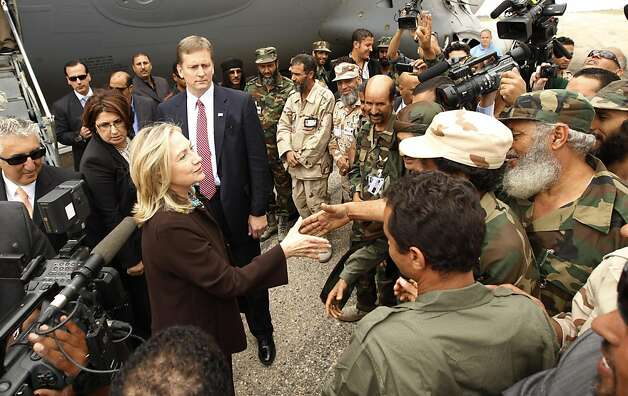 U.S. Secretary of State Hillary Rodham Clinton meets Libyan soldiers at the steps of her C-17 military transport upon her arrival in Tripoli in Libya, Tuesday Oct. 18, 2011. The Obama administration on Tuesday increased U.S. support for Libya's new leaders as Secretary of State Hillary Rodham Clinton made an unannounced visit to Tripoli and pledged millions of dollars in new aid, including medical care for wounded fighters and additional assistance to secure weaponry that many fear could fall into the hands of terrorists.  (AP Photo/Kevin Lamarque, Pool) Photo: Kevin Lamarque, AP