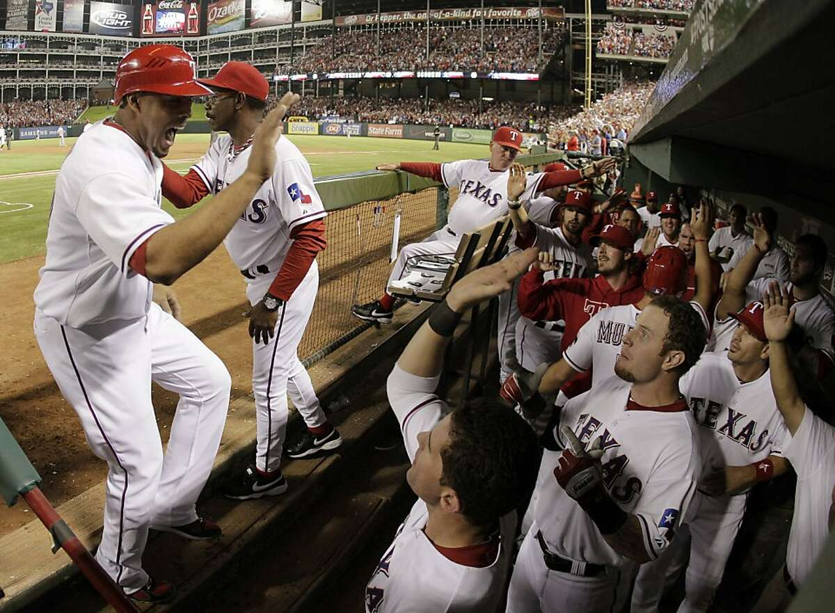 Texas Rangers' Nelson Cruz reacts after scoring on a double by Ian Kinsler during the third inning of Game 6 of baseball's American League championship series against the Detroit Tigers Saturday, Oct. 15, 2011, in Arlington, Texas. (AP Photo/Charlie Riedel)