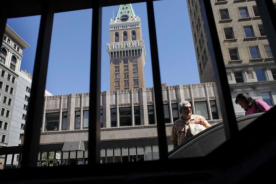 People get on and off of BART with the old Oakland Tribune building still sits in along 13th street among the newer high risers, Thursday August 25, 2011, in Oakland, Calif. The Oakland Tribune which is now the East Bay Tribune and yet another loss of identity for the East Bay's largest city.  Ran on: 08-26-2011 The Tribune tower is the Oakland skyline's most recognizable feature, even though the newspaper no longer operates there. Ran on: 08-26-2011 The Tribune tower is the Oakland skyline's most recognizable feature, even though the newspaper no longer operates there. Ran on: 08-26-2011 The Tribune tower is the Oakland skyline's most recognizable feature, even though the newspaper no longer operates there. Ran on: 08-26-2011 The Tribune tower is the Oakland skyline's most recognizable feature, even though the newspaper no longer operates there. Photo: Lacy Atkins, The Chronicle