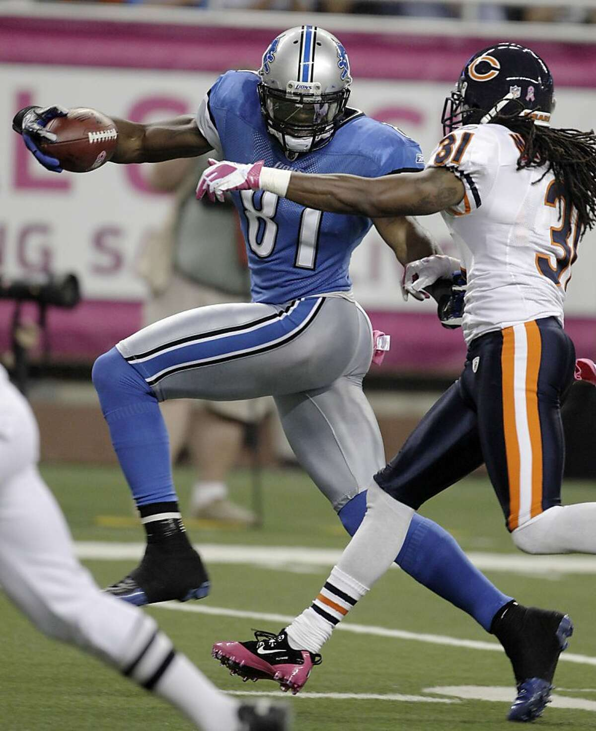Detroit Lions wide receiver Calvin Johnson (81) pulls away from Chicago Bears free safety Brandon Meriweather (31) on a 73-yard touchdown reception during the second quarter of an NFL football game in Detroit, Monday, Oct. 10, 2011. (AP Photo/Carlos Osorio)
