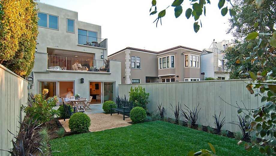 From the rear yard, the home's multiple levels and patios are visible. Photo: Sean Poreda