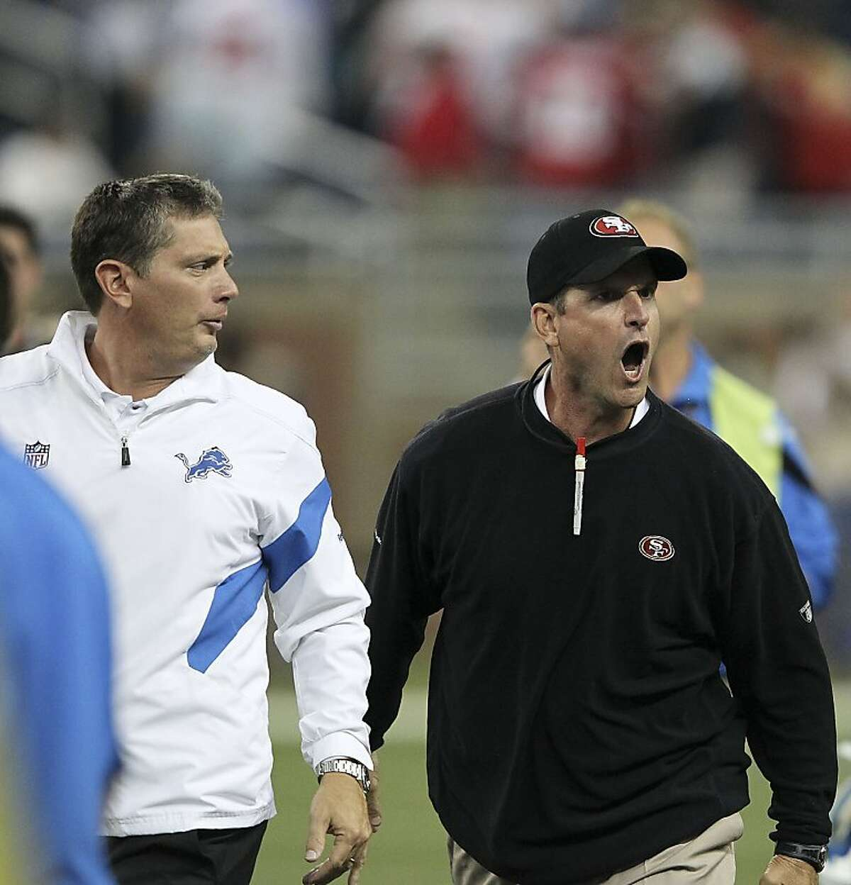 DETROIT - OCTOBER 16: Jim Harbaugh head coach of the San Francisco 49ers argues with Jim Schwartz of the Detroit Lions during the NFL game at Ford Field on October 16, 2011 in Detroit, Michigan. The 49ers defeated the Lions 25-19. (Photo by Leon Halip/Getty Images)
