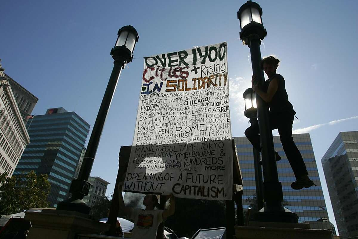 Nathan Smith slides down a light pole after hanging a sign in Frank Ogawa Plaza, site of Occupy Oakland, on Monday, Oct. 17, 2011, in Oakland, Calif.