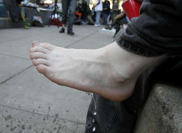 A young protester washed his feet with water from a cup. The OccupySF movement took some time to rest Monday October 17, 2011 after a police action to remove the tarps on their occupation at Justin Herman Plaza at the foot of Market Street in San Francisco, Calif. resulted in some arrests. Photo: Brant Ward, The Chronicle