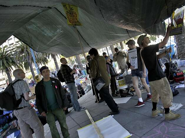 Protesters and their supporters worked to stabilize some tarps at the encampment. The OccupySF movement took some time to rest Monday October 17, 2011 after a police action to remove the tarps on their occupation at Justin Herman Plaza at the foot of Market Street in San Francisco, Calif. resulted in some arrests. Photo: Brant Ward, The Chronicle