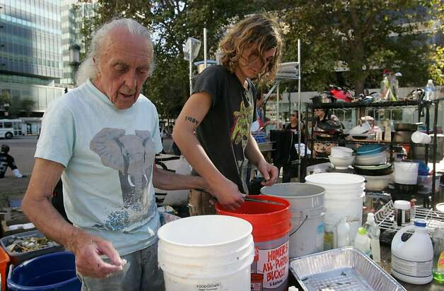 Martin Devido, 23, (R) and another volunteer, 73, wash dishes in the kitchen in Frank Ogawa Plaza, site of Occupy Oakland, on Monday, Oct. 17, 2011, in Oakland, Calif. Photo: Mathew Sumner, Special To The Chronicle