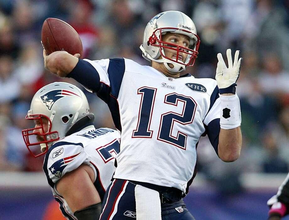New England Patriots quarterback Tom Brady (12) throws as guard Logan Mankins protects against the Dallas Cowboys during an NFL football game in Foxborough, Mass. Sunday, Oct. 16, 2011. (AP Photo/Elise Amendola) Photo: Elise Amendola, AP