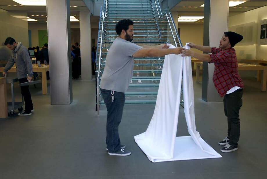 Apple Store employees fold white curtains, used to cover the windows at the Stockton Street location, before the store reopens at noon in San Francisco, Calif. on Wednesday, Oct. 19, 2011 after it was closed during the morning so employees could watch a broadcast of a private memorial service for Steve Jobs. Photo: Paul Chinn, The Chronicle