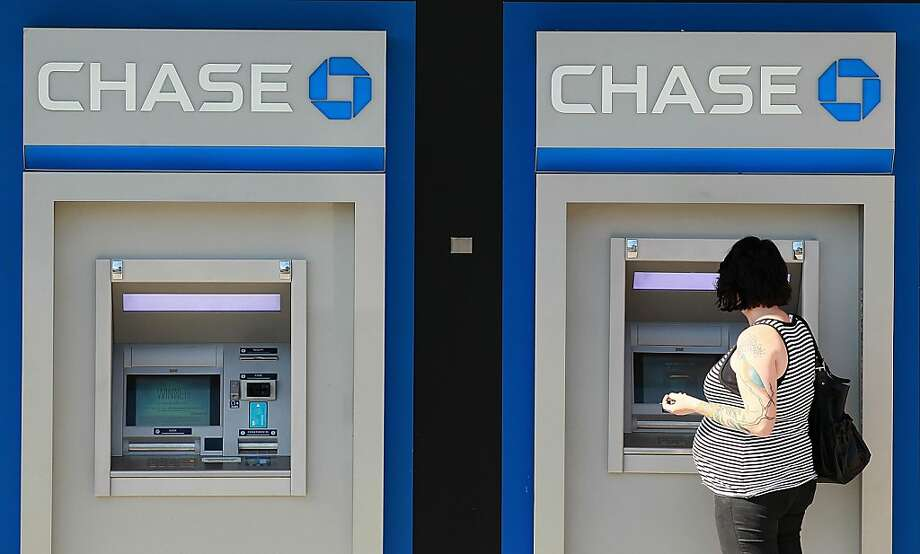 OAKLAND, CA - OCTOBER 13:  A customer uses an ATM outside of a Chase bank office on October 13, 2011 in Oakland, California.  JPMorgan Chase & Co. a nearly 33 percent decline in third quarter profits with earnings of $3.1 billion compared to $4.71 billion one year ago.  (Photo by Justin Sullivan/Getty Images) Photo: Justin Sullivan, Getty Images