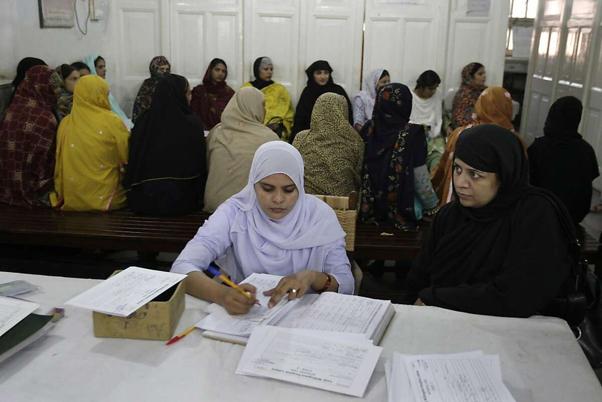 In this Oct. 12, 2011 photo, a pregnant woman gets a check up slip from a nurse as others wait for their turn at Lady Willingdon hospital in Lahore, Pakistan. The government of Pakistan's most populous province, Punjab, turned down an American offer of $127 million for health care, education and municipal services following the U.S. raid that killed Osama bin Laden. Sixteen million dollars had been earmarked for the hospital. The impact of an aid cut in this poverty-stricken country would be felt most acutely by the poorest citizens. (AP Photo/K.M. Chaudary)