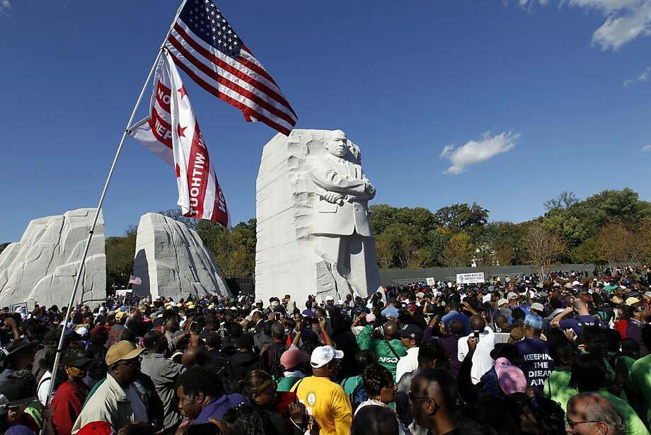 Demonstrators crowd around the new Martin Luther King Jr. Memorial during a rally and march of thousands in Washington Saturday, Oct. 15, 2011. Civic leaders, led by the Rev. Al Sharpton, rallied for easier access to jobs. (AP Photo/Jose Luis Magana) Ran on: 10-16-2011 Demonstrators march to the new Martin Luther King Jr. Memorial in Washington, which will be dedicated today. Photo: Jose Luis Magana, AP