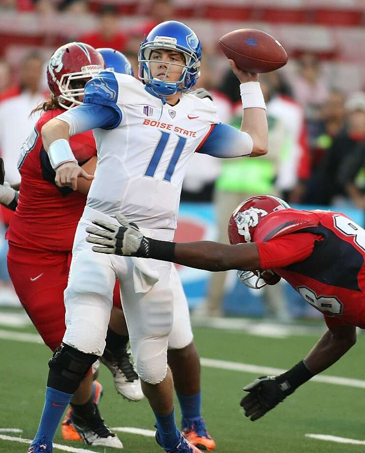 Boise State's Kellen Moore (11) throws a touchdown pass in the first half of an NCAA college football game against the Fresno defense, Friday, Oct. 7, 2011, in Fresno, Calif.  Boise State won 57-7. Moore went 23 of 31 for 254 yards and three scores in this 43rd career win. (AP Photo/Gary Kazanjian) Photo: Gary Kazanjian, AP