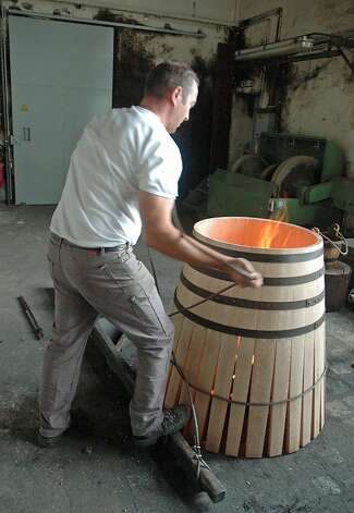 A cooper tightens the cords to compress a cognac barrel. Photo: Bill Fink, Special To The Chronicle