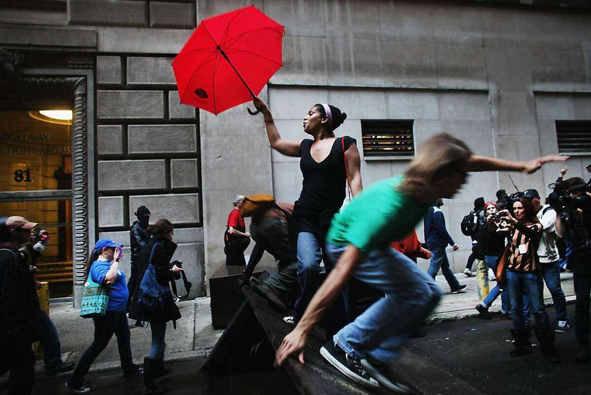 NEW YORK, NY - OCTOBER 14: Demonstrators associated with the 'Occupy Wall Street' jump over barricades as they face off with police in the streets of the financial district after the deadline for their removal from Zuccotti park was postponed on October 14, 2011 in New York City. Many of the 'Occupy Wall Street' demonstrators have been living in Zuccotti Park in the Financial District near Wall Street. The activists have been gradually converging on the financial district over the past three weeks to rally against the influence of corporate money in politics among a host of other issues. The protests have begun to attract the attention of major unions and religious groups as the movement continues to grow in influence. Dozens of protesters were arrested in the morning demonstrations. (Photo by Spencer Platt/Getty Images)