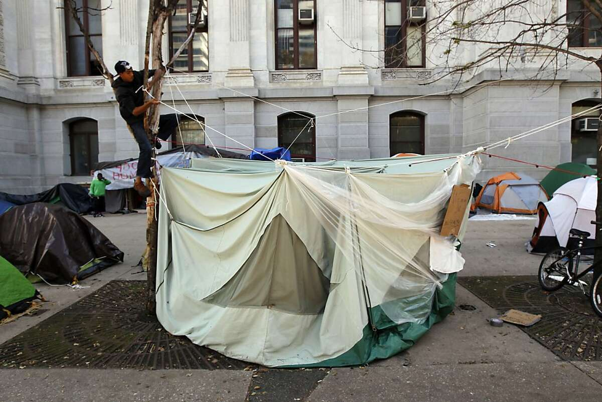 Nicholas Molinuevo, left in tree, works on his tent in the park around City Hall Sunday, Oct. 16, 2011 in Philadelphia. The demonstration at City Hall is one of many being held across the country in support of the ongoing Occupy Wall Street demonstration in New York. (AP Photo/Alex Brandon)