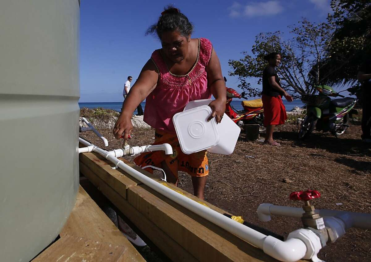In this Oct. 13, 2011 photo, residents collect their morning ration of fresh water made from desalinated sea water in Funafuti, Tuvalu, South Pacific. Funafuti is the capital of Tuvalu, a group of atolls situated north of Fiji and northwest of Samoa, in the South Pacific ocean. The atolls are suffering a severe drought and water shortage, coupled with contaminated ground water due to rising sea levels. The governments of Australia, New Zealand and the United States are providing desalination plants to alleviate the critical water shortage for some 10,000 islanders. (AP Photo/Alastair Grant) Ran on: 10-15-2011 Residents collect their morning ration of freshwater in Funafuti, Tuvalu.