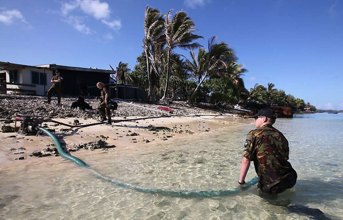 In this Oct. 13, 2011 photo, members of the Royal New Zealand defense force pump sea water into large holding tanks ready to be used by the desalination plant in Funafuti, Tuvalu, South Pacific. Funafuti is the capital of Tuvalu, a group of atolls situated north of Fiji and northwest of Samoa, in the South Pacific ocean. The atolls are suffering a severe drought and water shortage, coupled with contaminated ground water due to rising sea levels. The governments of Australia, New Zealand and the United States are providing desalination plants to alleviate the critical water shortage for some 10,000 islanders. (AP Photo/Alastair Grant) Ran on: 10-15-2011 Royal New Zealand military members pump seawater into holding tanks to be used by the desalination plant in Funafuti, Tuvalu, an area in the South Pacific where limited freshwater is available.