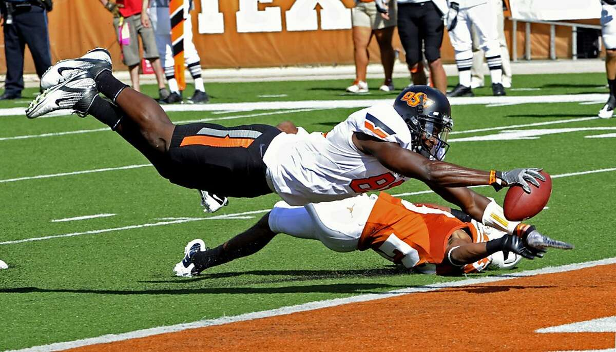 Oklahoma State's Justin Blackmon, front, dives into the end zone for a touchdown as Texas cornerback Carrington Byndom, back, defends during the second quarter of an NCAA college football game, Saturday, Oct. 15, 2011, in Austin, Texas. (AP Photo/Michael Thomas)