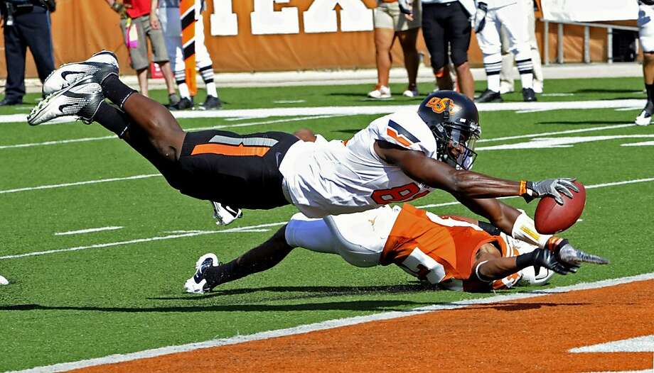 Oklahoma State's Justin Blackmon, front, dives into the end zone for a touchdown as Texas cornerback Carrington Byndom, back, defends during the second quarter of an NCAA college football game, Saturday, Oct. 15, 2011, in Austin, Texas.  (AP Photo/Michael Thomas) Photo: Michael Thomas, AP