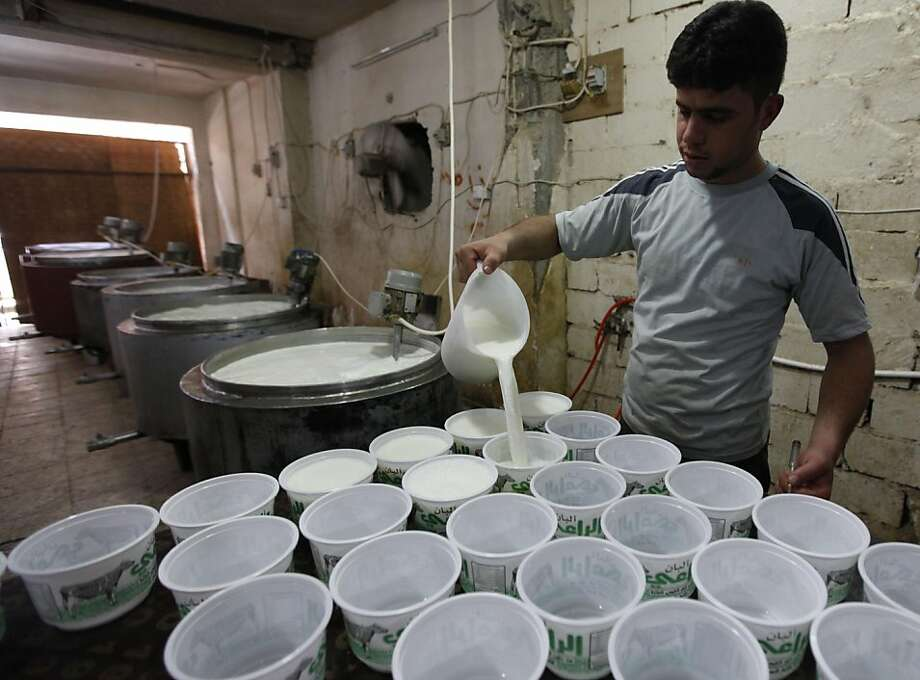 In this Sunday, Aug. 7, 2011 photo, a worker pours yogurt into containers at a small milk products factory in Fallujah, 40 miles (65 kilometers) west of Baghdad, Iraq. The U.S.-led invasion eight years ago provided an opportunity to liberate Iraqis not only from Saddam Hussein's oppression, but also from a command-and-control economy dependent on oil revenues. But when the last U.S. troops withdraw from Iraq by the end of the year, they will leave behind a nation in which widespread corruption, bureaucratic hurdles and electricity shortages continue to stifle the economy. (AP Photo/Hadi Mizban) Photo: Hadi Mizban, AP