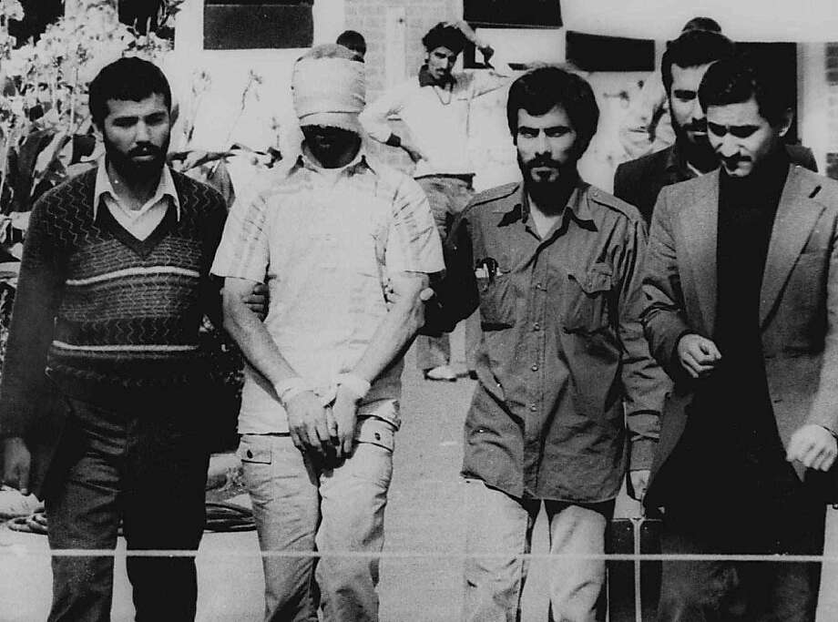 ** FILE ** In this Nov. 9, 1979 file photo, one of the hostages seized when Islamic radicals stormed the U.S. Embassy in Tehran, blindfolded and with his hands bound, is displayed to the crowd outside the U.S. Embassy in Tehran by the Iranian hostage takers. Although President Carter worked throughout the 1980 presidential campaign to secure the release of the hostages, he failed and they were not released until Ronald Reagan was inaugurated.  (AP Photo/File)  Ran on: 10-16-2011 The capture of American hostages in Iran epitomized the country's low ebb in 1979, when we suffered an energy crisis, hyperinflation and high joblessness. Ran on: 10-16-2011 The capture of American hostages in Iran epitomized the country's low ebb in 1979, when we suffered an energy crisis, hyperinflation and high joblessness. Photo: AP