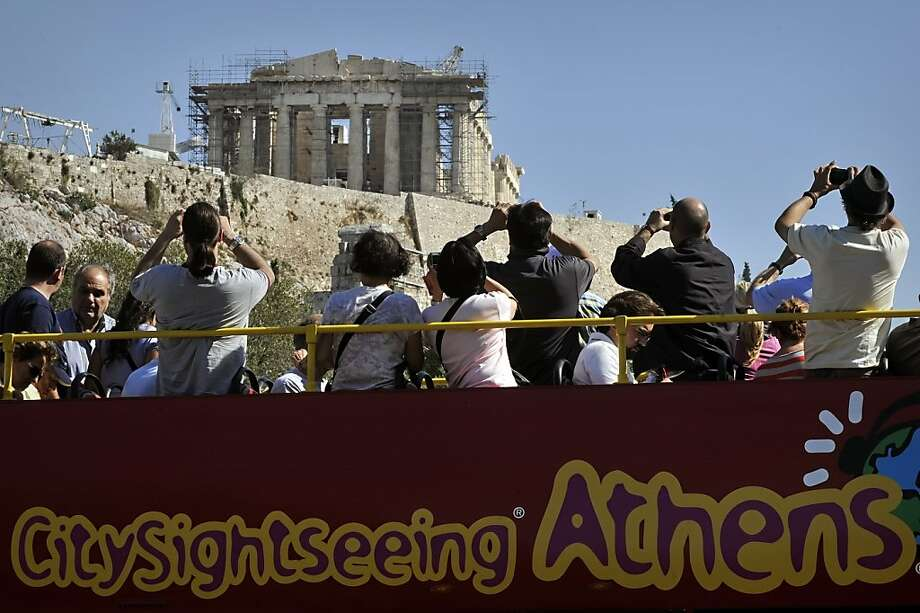 Tourists take photos of the shut down site of the Acropolis, from the top of a tour bus, during a 48-hour strike by Culture Ministry employees, on October 13, 2011. Public transport and public sector employees are on strike, after final talks between the government and EU-IMF creditors, ahead of a planned general strike on October 19 . AFP PHOTO / LOUISA GOULIAMAKI (Photo credit should read LOUISA GOULIAMAKI/AFP/Getty Images) Photo: Louisa Gouliamaki, AFP/Getty Images