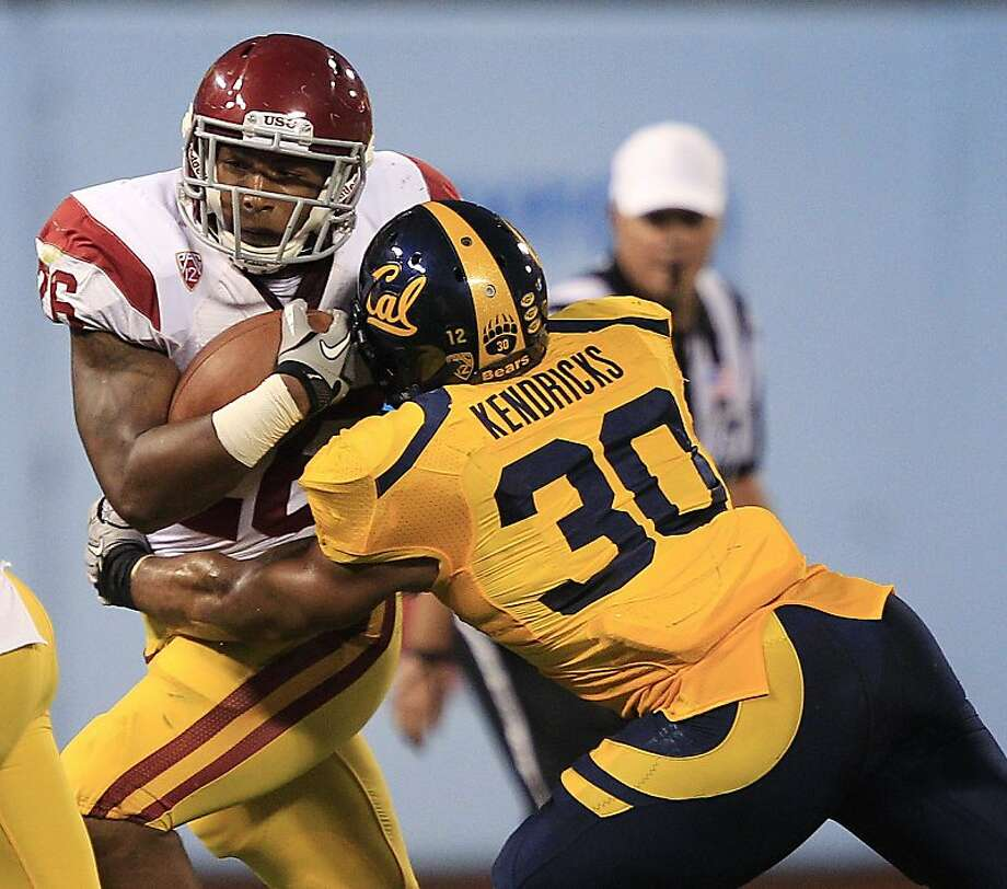 Southern California running back Marc Tyler (26) is tackled by California linebacker Mychal Kendricks (30) during the second quarter of an NCAA college football game in San Francisco, Thursday, Oct. 13, 2011. (AP Photo/Marcio Jose Sanchez) Photo: Marcio Jose Sanchez, AP