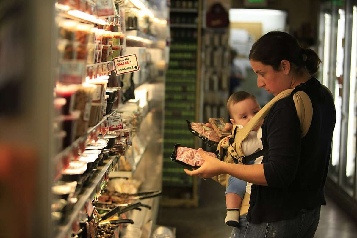 Lisa Brady of San Francisco selects groceries at Bi-Rite Market with her son, Oliver, 5 months, at Bi-Rite Market in San Francisco, Calif. on Monday November 23, 2009. Ran on: 11-26-2009 Lisa Brady of San Francisco selects groceries at Bi-Rite Market with her 5-month-old son, Oliver.