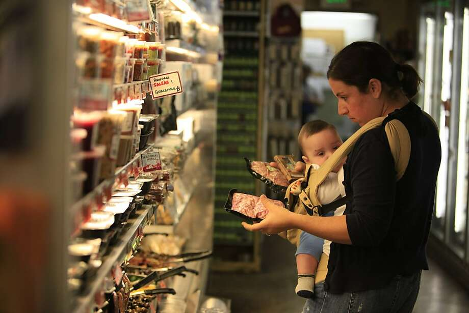 Lisa Brady of San Francisco selects groceries at Bi-Rite Market with her son, Oliver, 5 months, at Bi-Rite Market in San Francisco, Calif. on Monday November 23, 2009.   Ran on: 11-26-2009 Lisa Brady of San Francisco selects groceries at Bi-Rite Market with her 5-month-old son, Oliver. Photo: Lea Suzuki, The Chronicle