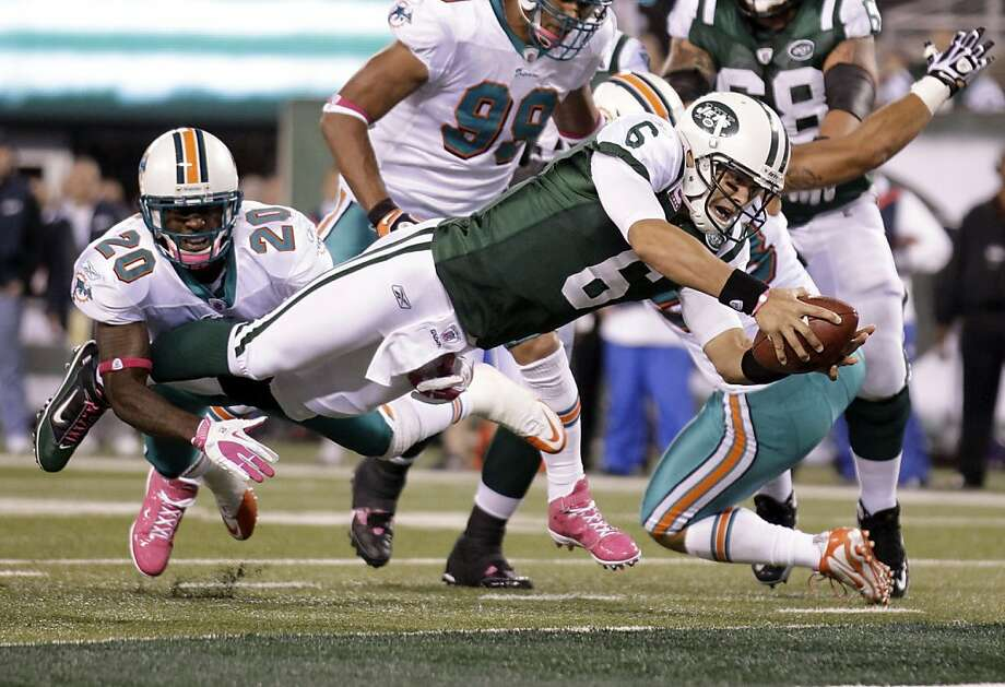 New York Jets quarterback Mark Sanchez (6) dives away from Miami Dolphins free safety Reshad Jones (20) for a touchdown during the second quarter of an NFL football game Monday, Oct. 17, 2011, in East Rutherford, N.J. (AP Photo/Julio Cortez) Photo: Julio Cortez, AP