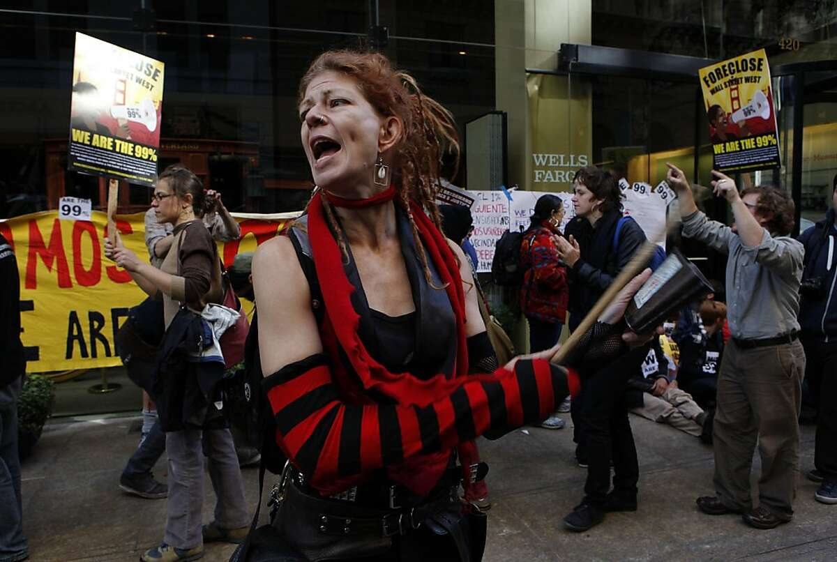 A member of the Brass Liberation Orchestra beats a cowbell as she joins fellow protesters in the Occupy Wall Street campaign as many blocked the entrances into the headquarters of Wells Fargo Bank in the financial district of San Francisco, Ca., on Wednesday October 12, 2011.