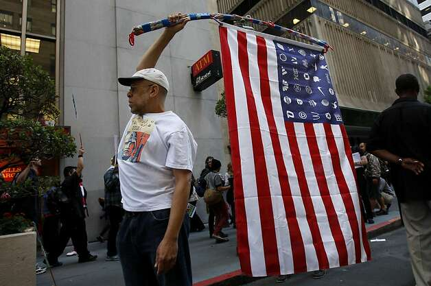 A man held a flag with corporate logos where stars should be. Demonstrators from various groups including OccupySF blockaded the doors of the Wells Fargo corporate headquarters on California Street in San Francisco, Calif. Wednesday October 12, 2011. Photo: Brant Ward, The Chronicle