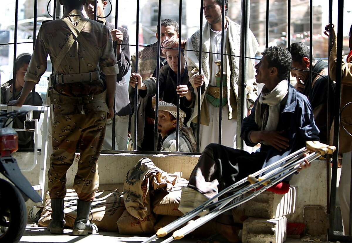 Yemeni sit outside the gates of makeshift hospital in the pro-democracy Change Square in the heart of Sanaa as they wait for news of their relatives who were wounded in overnight clashes, on October 17, 2011. Eight people were killed in overnight clashes in Sanaa as tension spiked following a new wave of killings of anti-regime protesters by troops loyal to veteran President Ali Abdullah Saleh. AFP PHOTO/MARWAN NAAMANI (Photo credit should read MARWAN NAAMANI/AFP/Getty Images)